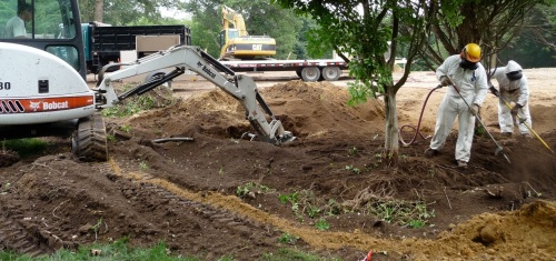 Bobcat continually takes blown soil out of the trench and stockpiles it.